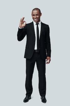 모든것이 완벽 해. 회색 배경에 서서 카메라를 보고 몸짓을 하는 정장을 입은 잘생긴 젊은 아프리카 남자의 전체 길이