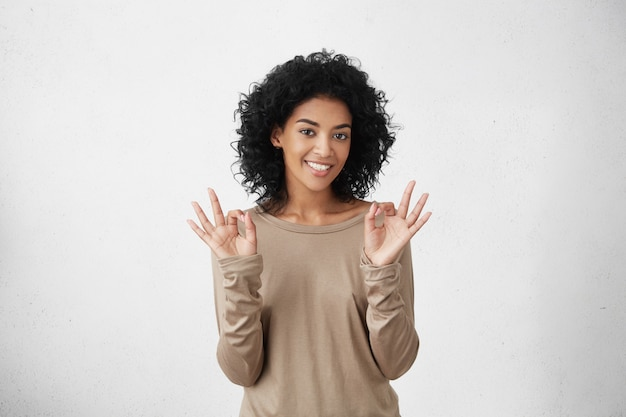 Everything is perfect. happy positive dark-skinned student woman showing ok gesture with both hands, having good mood after passing all exams at college successfully.