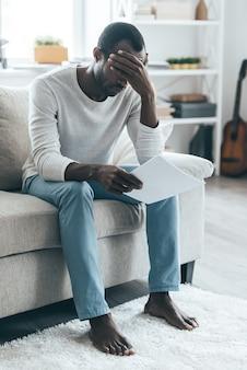 全部間違っている。自宅のソファに座っている間彼の目に手を握って欲求不満の若いアフリカ人