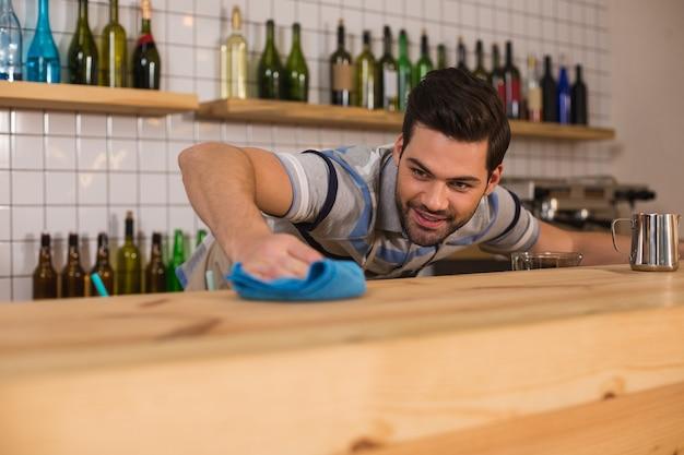 모든 것이 빛나야합니다. 카페테리아에서 일하는 동안 앞치마를 입고 카운터를 청소하는 즐거운 멋진 잘 생긴 남자