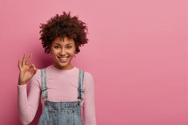 すべて大丈夫です。笑顔の暗い肌の女性はすべて制御されており、肯定的な回答をし、良い製品を推奨し、物事がうまくいっていることを確認し、何かが好きで、喜んで見え、屋内に立っています