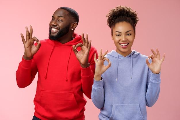 すべてが完璧です。魅力的な愛情のある2つのカップルの関係アフリカ系アメリカ人のガールフレンドのボーイフレンドは大丈夫okを示しています優れたジェスチャー笑顔の承認は両親に元気なピンクの背景を保証します