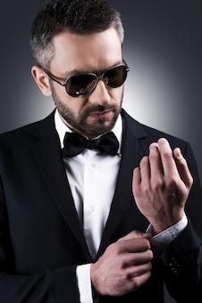 すべてが完璧でなければなりません。灰色の背景に立っている間彼の袖を調整するサングラスと正装でハンサムな成熟した男
