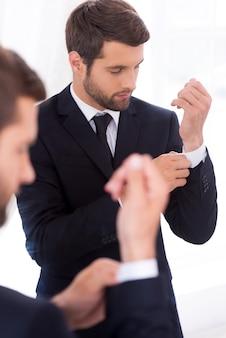 Все должно быть идеально. красивый молодой человек в строгой одежде поправляет рукава, стоя у зеркала