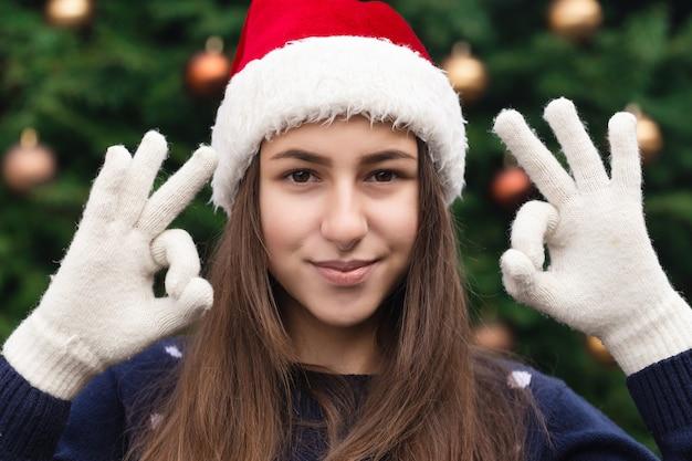 На рождество все будет хорошо. крупным планом портрет женщины в шляпе санта-клауса с эмоциями. на фоне елки.