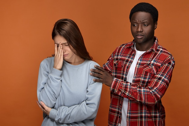 Tutto andrà bene. frustrata triste giovane donna bianca che copre il viso, sentendosi stressato a causa dei problemi sul lavoro, la sua comprensione amorevole fidanzato africano che esprime cura, simpatia e sostegno