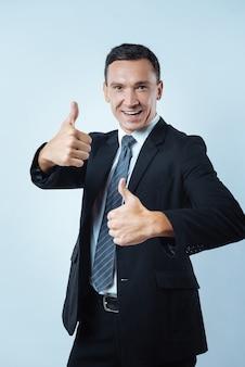 すべてが素晴らしいでしょう。幸せな前向きな陽気な男は、親指を立てるジェスチャーで手を握りながら、笑顔で楽観的な見方を示しています