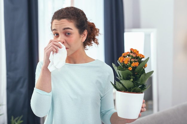Evidence of illness. young teary-eyed lady staying indoors while discovering an allergy condition provoked by blooming plants