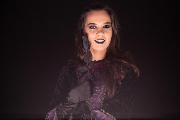 장미와 검은 배경 위에 사악하고 무서운 여성 마녀. 할로윈 복장.