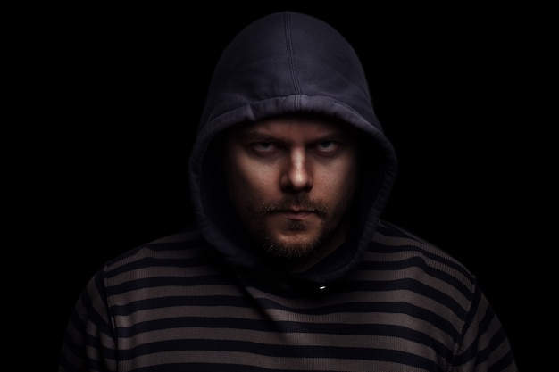 Злой драматический портрет человека в капюшоне на черном фоне