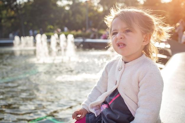 邪悪な表情顔。彼女がしかめっ面し、屋外の日当たりの良い公園で笑顔を見せている小さな怒っている幼児の女の子の肖像画