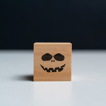 Evil face on a wooden cube halloween holiday