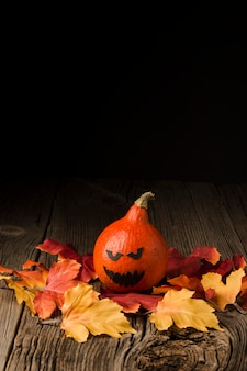 Evil halloween pumpkin with autumn leaves