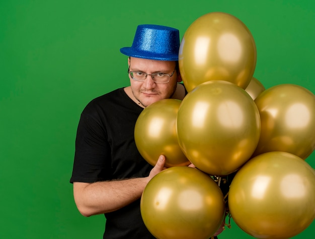 Evil joyful adult slavic man in optical glasses wearing blue party hat holds helium balloons