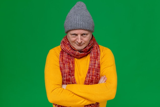 Evil joyful adult slavic man with winter hat and scarf around his neck standing with crossed arms and
