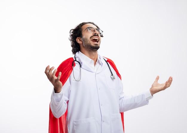 사악한 즐거운 젊은 백인 슈퍼 히어로 남자가 빨간 망토와 목에 청진기 의사 유니폼을 입고 광학 안경에 손을 열고 보유하고 흰색 벽에 고립 된 보인다