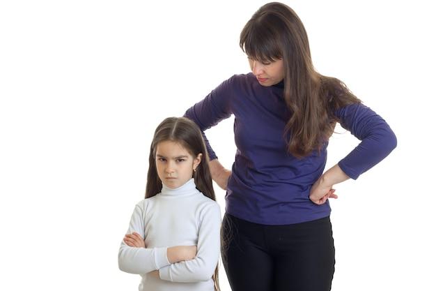 사악한 어린 소녀와 그녀의 엄마는 흰색 배경에 고립