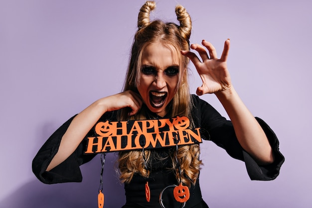 Evil witch funny posing in halloween. blonde girl having fun at carnival party.
