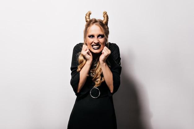 Злая ведьма с милой прической позирует на белой стене. смешная кавказская девушка позирует в хэллоуин в костюме волшебника.