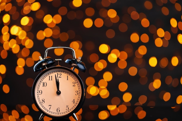 Ew year eve concept with alarm clock against blurred garland background