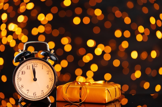 Ew year eve concept with alarm clock against blurred garland