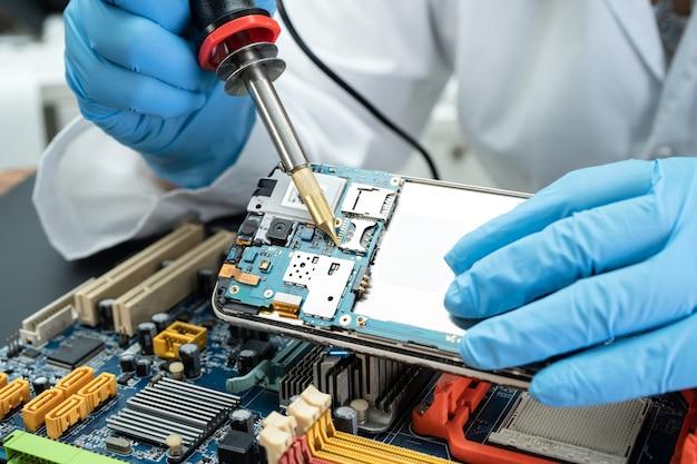Ewaste technician repairing inside of hard disk by soldering iron