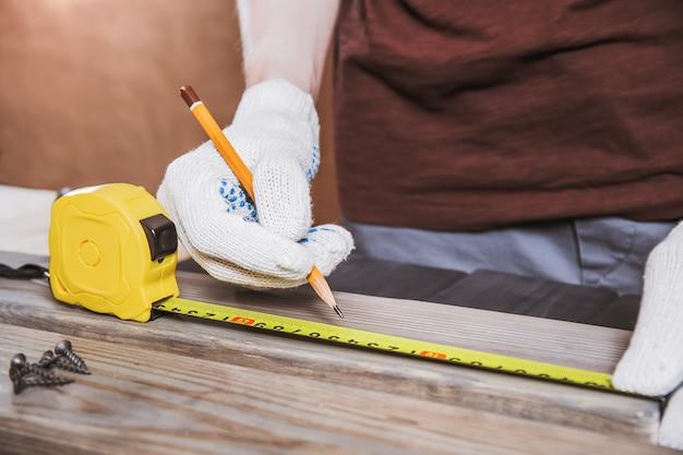 正確に測定。黄色のメジャーテープで木の板を測定する手袋をはめた若い男性の大工のクローズアップ。
