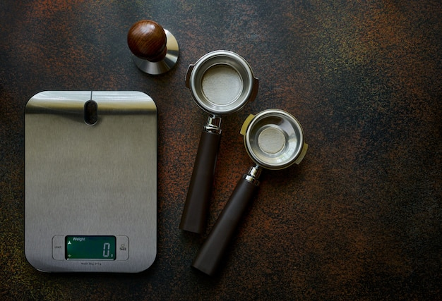 Exact scales and portofilters for coffee on a dark background with copy space, espresso recipe concept
