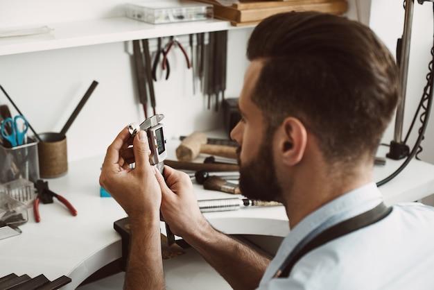 正確なサイズ。ワークショップでツールを使用してリングを測定する若い男性の宝石商の写真を閉じます。ジュエリー製造コンセプト。ジュエリー作りのワークショップ。マスターの手