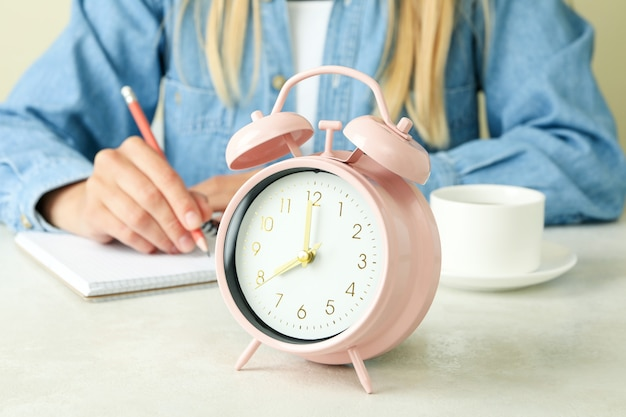 Exam concept with girl and alarm clock, close up