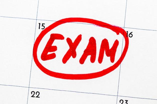 「exam」は、カレンダーに赤いマーカーで書かれたテキストです。