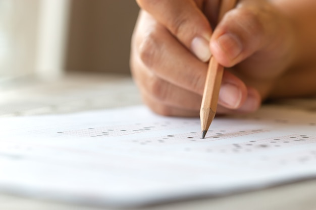 Exam test school or university concept : hand student holding pencil writing standardized answer multiple carbon paper form with gray black answers sheet bubbled of question in examination assessment.