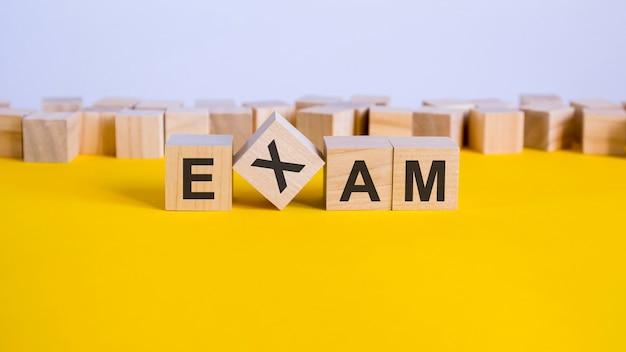 試験の単語は、黄色のテーブル、コンセプトに横たわっている木製のビルディングブロックで作られています