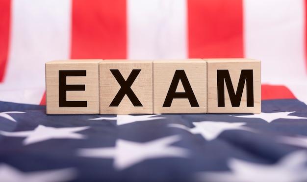 Слово экзамена на деревянных кубиках на американском флаге.