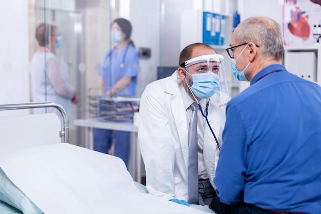 コロナウイルスに対する安全予防策として、病室で聴診器を使用し、フェイスマスクを着用して患者の心拍数を検査する