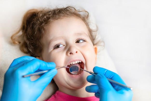検査、治療歯の子供たち。器具による健康診断口腔。歯科の手、クリニックの子供。