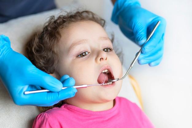 検査、治療歯の子供たち。器具による健康診断口腔。歯科の手、オフィスの子供。口腔病学を笑っているかわいい女の子。歯科医の椅子の子供。