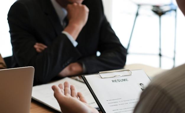 Экзаменатор, читающий резюме во время собеседования в офисе концепция бизнеса и человеческих ресурсов.