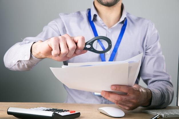 Осматривает бумагу с лупой на рабочем столе.