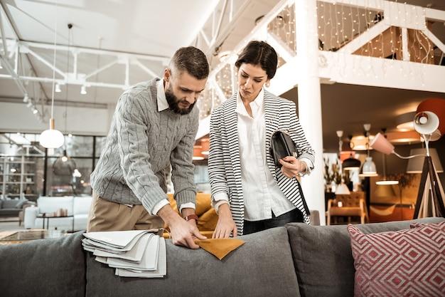 Осматриваем коричневый материал. задумчивая темноволосая дама выбирает образец легкой ткани, предложенный бородатым мужем