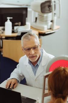 Изучая зрение. темноглазый профессиональный глазной врач чувствует себя занятым, исследуя зрение женщины