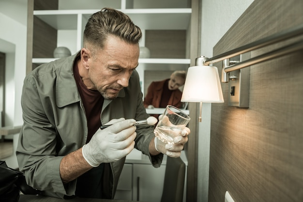 指紋の検査。彼の同僚が後ろで働いている間、犯罪者の古い指紋を探して透明なガラスを磨く気配りのある検査官