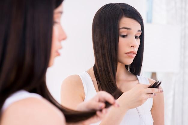 그녀의 손상된 머리카락을 검사합니다. 좌절한 젊은 여성이 그녀의 머리를 보고 거울에 기대어 서 있는 동안 부정성을 표현합니다