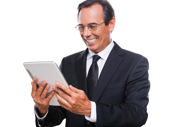 Осматривая свой новенький планшет. уверенный зрелый мужчина в строгой одежде держит цифровой планшет и смотрит на него с улыбкой, стоя изолированно на белом фоне