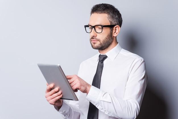 그의 새로운 태블릿을 살펴보고 있습니다. 회색 배경에 서서 디지털 태블릿 작업을 하는 셔츠와 넥타이를 입은 자신감 있는 성숙한 남자