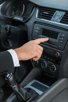 그의 새 차를 검사합니다. 차에 앉아있는 동안 손가락으로 대시보드를 만지는 정장을 입은 남자의 클로즈업