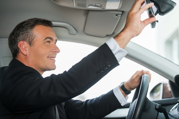 Examining his new car. side view of cheerful mature man in formalwear adjusting mirror while sitting in his car