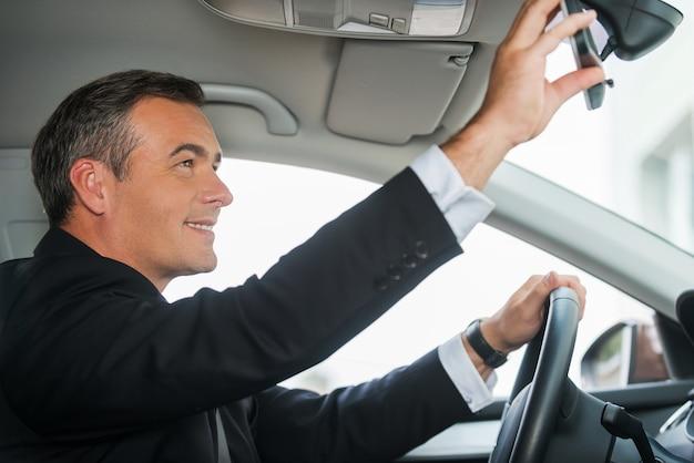 Осматривая свою новую машину. вид сбоку веселого зрелого мужчины в формальной одежде, регулирующего зеркало, сидя в своей машине