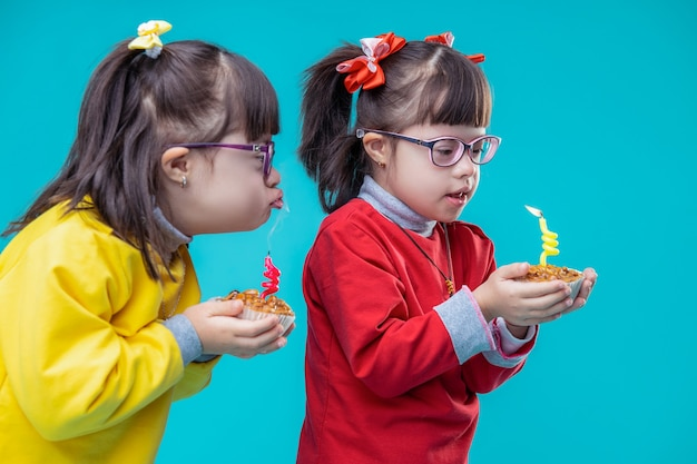 Examining holiday cakes. interested adorable sisters carrying cakes and blowing on candle while wishing dream