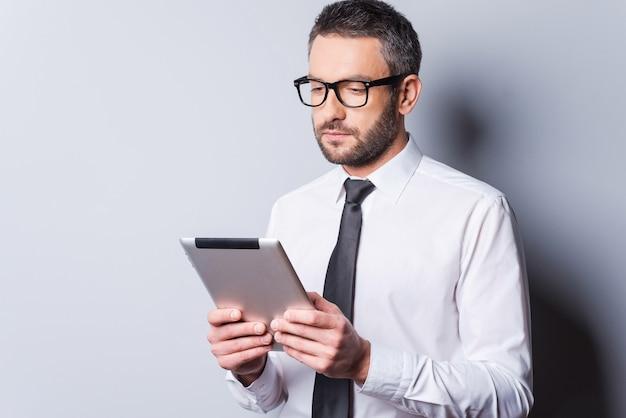 새 태블릿을 검토 중입니다. 셔츠에 넥타이를 매고 디지털 태블릿을 들고 회색 배경에 서서 그것을 바라보는 자신감 있는 성숙한 남자